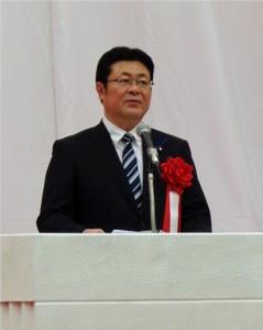 開会式で祝辞を述べる西村副大臣 (国立オリンピック記念青少年総合センター)