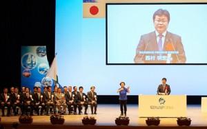 記念式典で挨拶する西村副大臣  (市民会館崇城大学ホール)